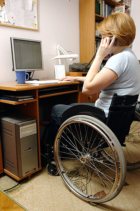 Lady in a wheelchair sitting at computer and talking on the phone