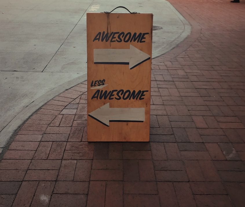 sandwich board saying Awesome, less awesome